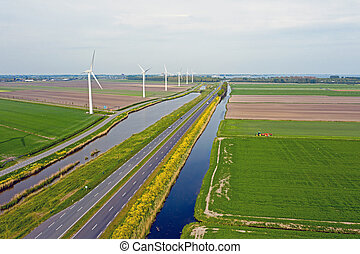 Aerial from a typical dutch landscape: Wind turbines, canals, straight roads and flat meadows in the countryside from the Netherlands