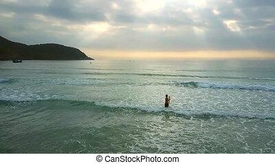 aerial girl holds surfboard walks on shallow ocean - aerial...