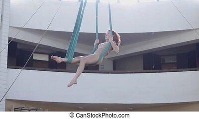 Aerial gymnast proceeds to circus and performs the splits in...