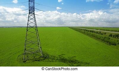 AERIAL High-voltage tower summer light sky background green...