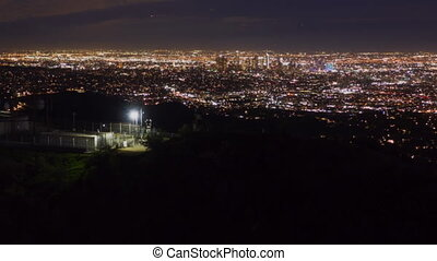 AERIAL HYPER LAPSE: Over Hollywood Sign at Night in Los Angeles, California at Night with Glowing Cityscape Time Lapse