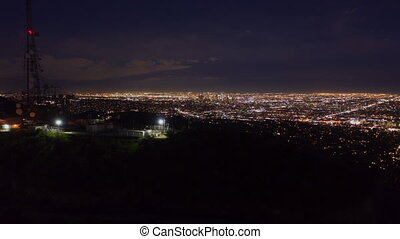AERIAL HYPER LAPSE: Over Hollywood Sign at Night in Los Angeles, California at Night with Glowing Cityscape Time Lapse 4K