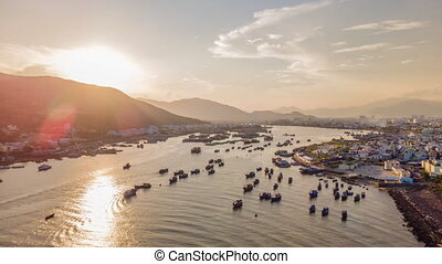 Aerial hyperlapse of the harbor of the city of Nha Trang. 2 hyperlapses in one clip. One during the day, and one during sunset. Travel to Vietnam concept