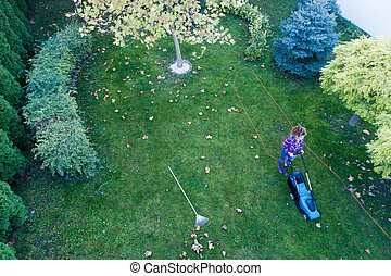 Aerial image of girl mowing lawn