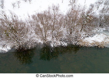 Aerial image of river in snowy forest