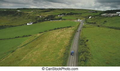Aerial Ireland's road view: cars riding on countryside green...