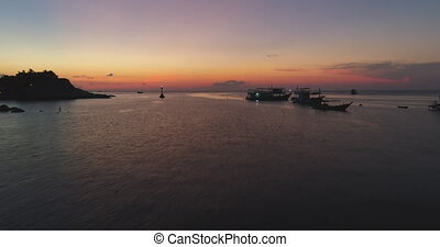 Aerial Island Seascape Sunset Boat Anchorage View. Motorboats Anchored Lighthouse Illumination Drone Rise up. Calm Sea Ripples Ocean Tide Seacoast Scenery Marine Natural Environment Thailand 4K