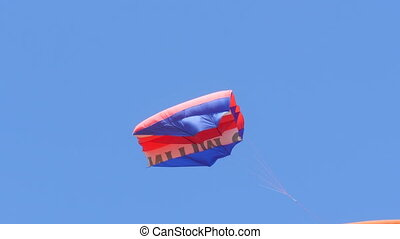 Aerial Kite - Batman Flies Against the Blue Cloudless Sky. His Blue Wings Tremble from the Incoming Air Streams. Festival of Kites on Summer Holidays.