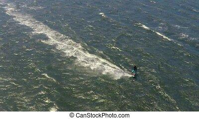 Aerial kite view of kitesurfer gliding across river on a...