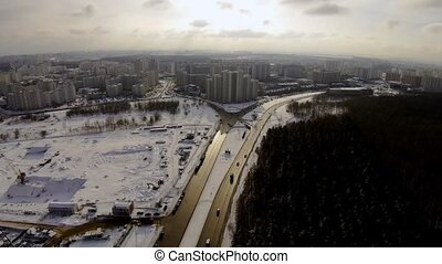 Aerial landscape of modern cityscape with road, forest and...