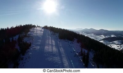 Aerial landscape snow slope with ski elevator in winter ski resort. Winter activity on luxury ski resort drone view.
