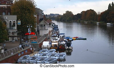 Aerial Landscape 4k video of Boats Docked on the River Nith alongside some buildings and with autumn trees as background