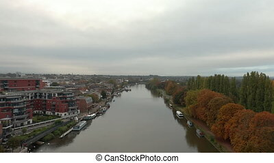 Aerial 4k video moving forward and Over the River Nith that Divides a Town and a Small Forest, with a cloudy sky as background