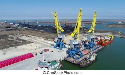 Aerial loading the Containers by crane , Trade Port , Shipping. Cranes for loading, unloading and sorting of containers. Container Cargo freight ship with working crane bridge in shipyard at dusk for Logistic