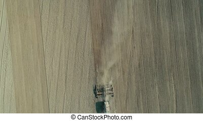Aerial: Lonely tractor plow the wheat field