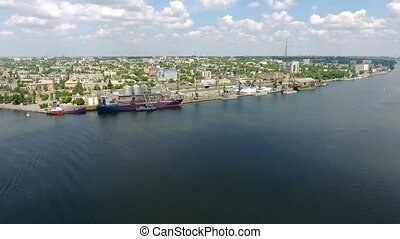 Aerial long shot of lofty cranes and docks in a port at the...