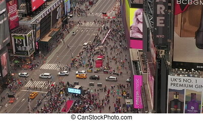 AERIAL: Look over Times Square heart of New York City at Daylight with crowd of people and heavy car traffic from above