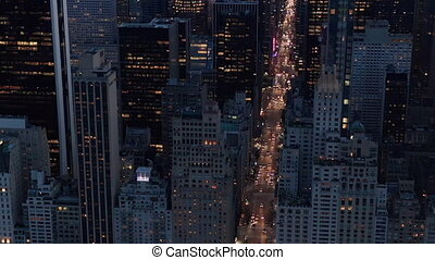 AERIAL: Manhattan Skyline at night with flashing City lights in New York City over Central Park