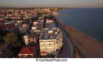 Aerial morning scene of small resort town on seashore,...