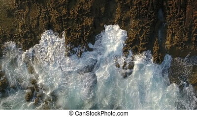 Aerial. Movements of waves splashing on the rocks, view from the sky.