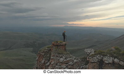Aerial - Moving around a young adult woman with a backpack reaching the top of the rock at the foot of the epic plateau at sunset. View from the back. Russia. North Caucasus