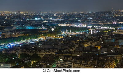 Aerial Night timelapse view of Paris City and Seine river shot on the top of Eiffel Tower