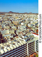 aerial of Arrecife with volcanoes at the horizon