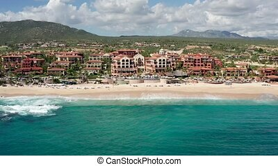 Aerial of coast line in Cabo, showing Sheraton Hacienda resort, waves crashing