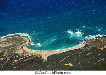 Aerial of coastline of Molokai with waves crashing into Mo'omomi beach