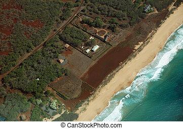 Aerial of Northwest coast beach of Molokai with waves crashing into shore