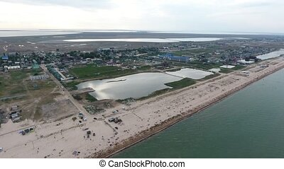 Inspiring bird`s eye view of a Black Sea seafront with straight beach, white sand, sunshades, weeds, small lakes, private houses in summer. It looks fine and cheery.