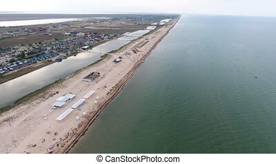 Magnificent bird`s eye view of a Black Sea sand spit with straight beach, white sand, sunshades, weeds, long lake in summer. It looks impressive and wild.