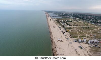 Marvelous bird`s eye view of a Black Sea coastline with straight beach, white sand, sunshades, grass, roads, small houses in summer. It looks cheery and rough.