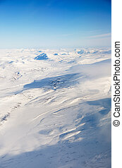 Aerial of Svalbard - A snow covered mountain landscape -...