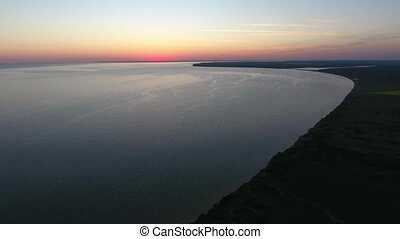 Aerial of the curvy Black Sea coast with an orange horizon...