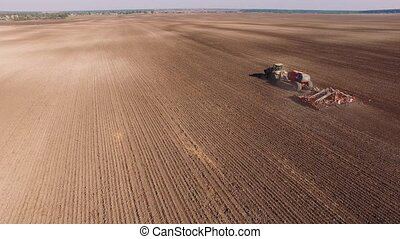 Aerial of tractor on harvest field top view from height