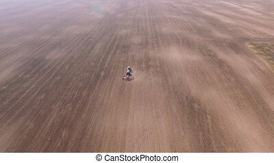 Aerial of tractor on harvest field top view from height -...