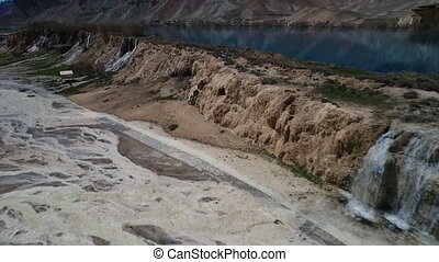 Aerial of waterfalls from blue lake into desert stream beds....