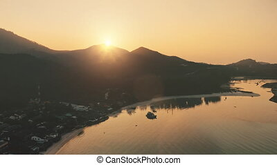 Aerial orange sunrise sky behind tropical island mountain and ocean bay. Nature background. Travel