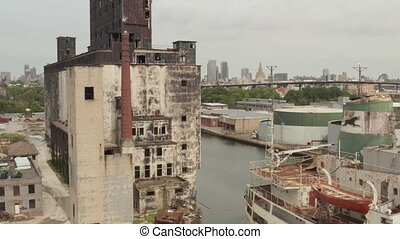AERIAL: Over Rusty old Cargo Ships and old Warehouse in the Docks of New York City on a cloudy Grey day