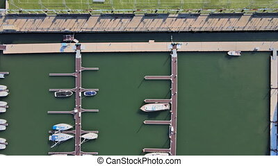 Aerial over small marina on a dock basin in small harbor, aerial view famous summer vacation tourist destination