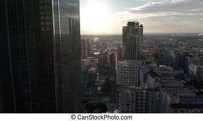Aerial pan between downtown Los Angeles LA street, California Plasa, Financial District at sunrise