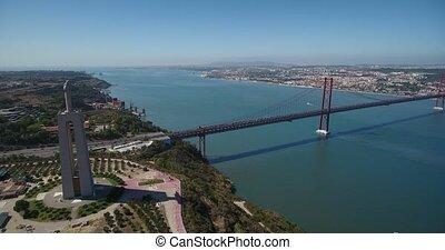 Aerial. Panorama from sky, a 25 de Abril Bridge and a statue of Jesus Christ. Lisbon