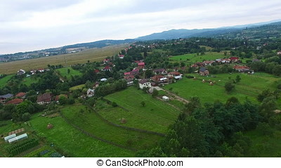 Aerial panorama of mountain village and green forest hills