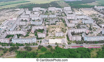 Aerial Panorama on City with Multi-Story Buildings near Nature and River. Top view on Dwelling Blocks. USSR apartments. Housing condominiums for families. Rooftops and facades. Fly over small town