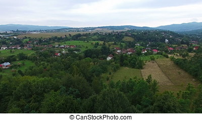 Aerial panorama over mountain village and green forest hills
