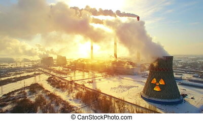 Aerial panoramic flight of hyperlaps around the nuclear thermal power plant. Winter morning is full of smoke and steam, chimneys smoke the sun rises and shines through clouds of smoke. Ecology and pollution of nature theme. Energy coal plant. Carbon dioxide emissions.