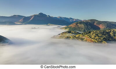Aerial panoramic view above foggy landscape in autumn. Slow motion time lapse flight
