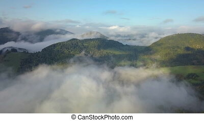 Aerial panoramic view above mist clouds in magic country landscape at morning sunrise