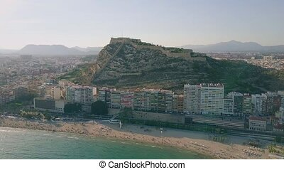 Aerial panoramic view of Alicante cityscape involving beachfront and Santa Barbara castle